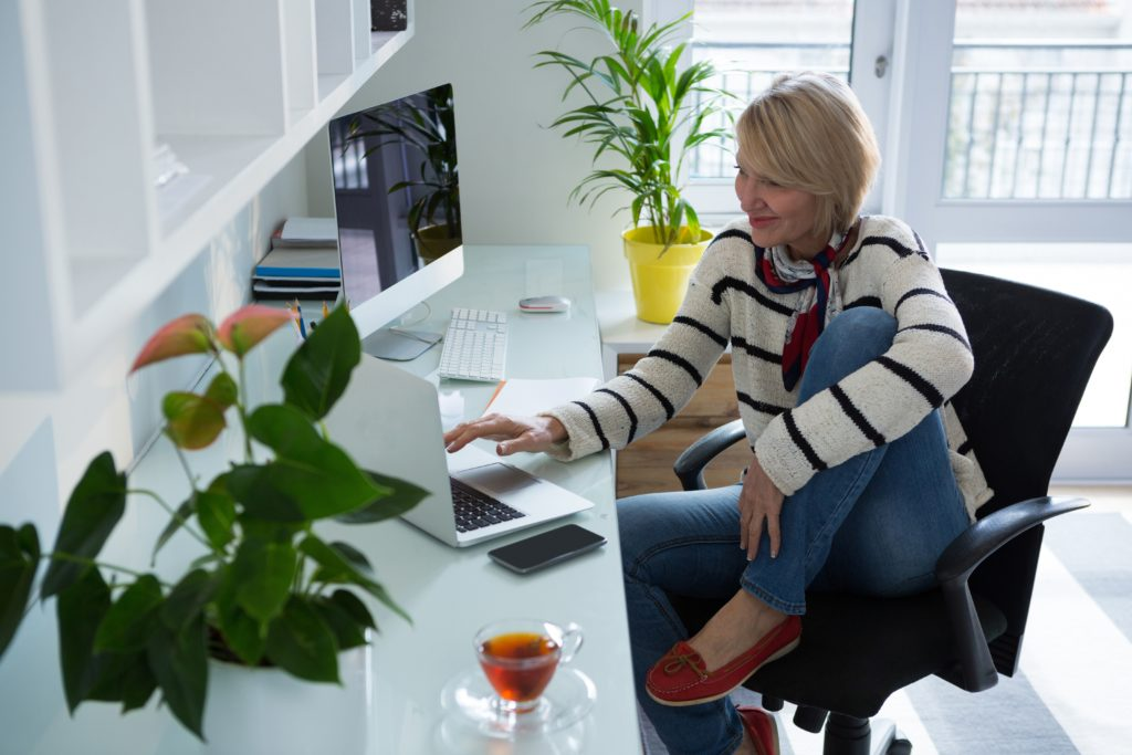 A woman sits at her desk in her home, working from a laptop.